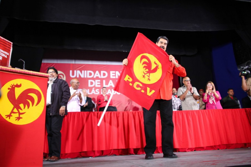 Venezuelan President Nicolas Maduro poses with the Venezuelan Communist Party's flag at the PCV's fourteenth national congress Monday, where it ratified him as their presidential candidate